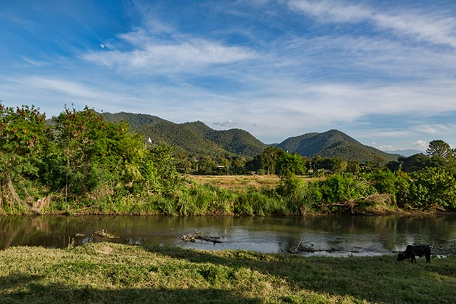 Pai river with the big Buddha in the mountain