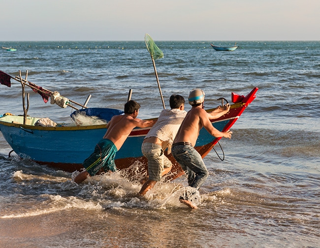 Putting the fishing boat into the water at the Beach in Hàm Tiến