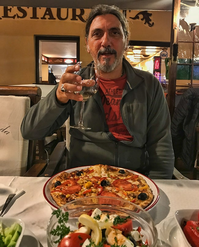 A happy Mitsos with food he understands and wine!