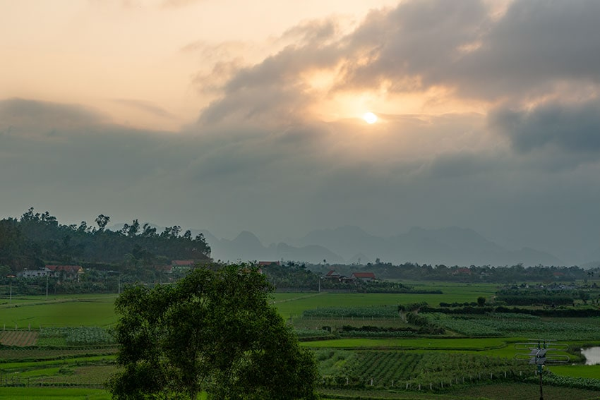 The sun sinking into the mountains at Phong Nha